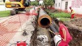 levantado : Zrenjanin, Vojvodina, Serbia - August 04, 2014: Excavator is holding isolated pipe over trench at building site until worker is cleaning dirt under. Vídeos