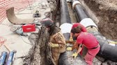 připevnění : Zrenjanin, Vojvodina, Serbia - August 04, 2014: Worker is aligning pipeline made of isolated pipes in trench at building site until he is tightening welding tool.