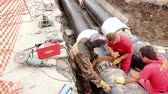 levantado : Zrenjanin, Vojvodina, Serbia - August 04, 2014: Worker is aligning pipeline made of isolated pipes in trench at building site until he is tightening welding tool.
