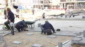 flagstone : Zrenjanin, Vojvodina, Serbia - March 09, 2015: Masons are fitting flagstone, view on construction site until they paving, building pavement. Stock Footage