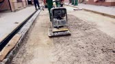 flatten : Vibrating machine is compacting soil at the constructioSoil compacting is at construction site in the city street. Vibration plate compactorn site. Stock Footage