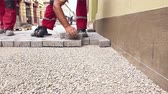 flagstone : Masons hands are fitting flagstone.Masons are fitting flagstone, low angle view until they making footpath in city street. Stock Footage