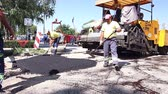 espalhando : Zrenjanin, Vojvodina, Serbia - August 19, 2014: Mason is using a trowel tool to finish surface of the tarmac, asphalt. Stock Footage