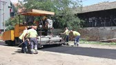 espalhando : Zrenjanin, Vojvodina, Serbia - August 19, 2014: Hot asphalt is applied to the street with construction machinery.