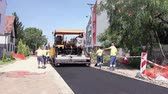 espalhando : Zrenjanin, Vojvodina, Serbia - August 19, 2014: Workers are spreading hot asphalt with shovels by removing excess material behind paving machine.