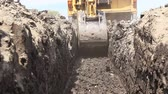 dredging : Zrenjanin, Vojvodina, Serbia - April 23, 2015: View from trench until excavator is excavating a ditch Low angle view on backhoe tractor until is digging a trench.