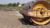 Huge road roller with spikes is compacting soil at construction site.