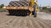 Construction worker is driving huge road roller with spikes and compacting soil for a large foundation Wideo