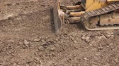 undercarriage : Heavy earthmover, bulldozer machine is leveling construction site View on bulldozer, crawler while he is moving and leveling ground at building site. Stock Footage