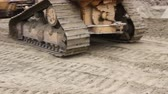 undercarriage : Crawlers tracks, bulldozer machine is leveling construction site Close up view on bulldozers undercarriage during pushing ground at construction site. Stock Footage