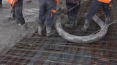 gelosia : Workers are spreading concrete over big reinforced floor on the construction site Construction workers are pouring concrete in building foundation, directing pump tube on the right direction. Stock Footage