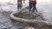 instalator : Workers are spreading concrete over big reinforced floor on the construction site Construction workers are pouring concrete in building foundation, directing pump tube on the right direction. Wideo