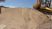 withdraw : Excavator is preparing pile of sand for loading in truck on building site Yellow excavator is making pile of soil by pulling ground up on heap at construction site, project in progress. Stock Footage
