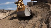 undercarriage : Excavator is preparing pile of sand for loading in truck on building site Yellow excavator is making pile of soil by pulling ground up on heap at construction site, project in progress. Stock Footage