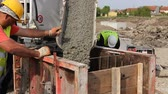 база : Zrenjanin, Vojvodina, Serbia - April 30, 2015: Workers at building site are pouring concrete in mold from mixer truck. Стоковые видеозаписи