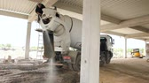 scour : Zrenjanin, Vojvodina, Serbia - May 28, 2015: Driver is washing mixer truck with water jet, after concrete casting.