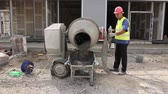 doldurulmuş : Zrenjanin, Vojvodina, Serbia - May 29, 2015: Worker is transport concrete over building site from cement mixer into wheelbarrow. Stok Video