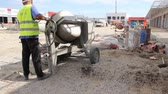 refill : Zrenjanin, Vojvodina, Serbia - May 29, 2015: Worker is pouring concrete from cement mixer into wheelbarrow.