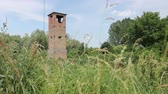 zanedbaný : Ancient abandoned lookout tower overgrown among grass vegetation. Old brick watch tower is overlooking ancient border crossing from Europe to Asia.