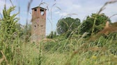 overview : Ancient abandoned lookout tower overgrown among grass vegetation. Old brick watch tower is overlooking ancient border crossing from Europe to Asia.
