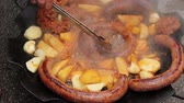 kleště : Turning delicious potato and juicy sausages on barbecue plate with handle.  Hand with the help of metal tongs turns the simmering potatoes and sausages on a black barbecue grill.