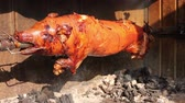 деликатес : Pigs are being grilled slowly on spit in traditional way, cooked with charcoal, fatty roasted meat, grilled pork over fire pit has being automatically turned. Стоковые видеозаписи