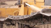 Close up view on bulldozers undercarriage during pushing ground at construction site. Wideo