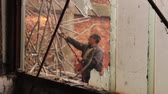 lakatosmunka : View trough broken window on worker who is cutting small tubes, obsolete industrial equipment with acetylene torch. Photo - JPEG video codec