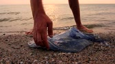 zatáčka : Man is with hand fingers is touching carcass of dead huge blue jellyfish washed up by the sea on sandy beach. Photo - JPEG video codec Dostupné videozáznamy