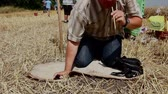 begraven : Muzlja, Vojvodina, Serbia - July 05, 2014: Tourist is kneeling and drinking schnapps with stalk of wheat straw from bottle buried in ground. Photo - JPEG video codec