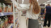 débito : Woman chooses Buying juice in the supermarket. Shopping in Grocery Store or Supermarket