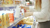 débito : Young woman in a dairy section of supermarket get a milk
