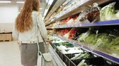 débito : Woman grocery shopping. Young woman chooses vegetables on store shelves. Stock Footage