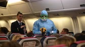 Moscow - March 04 2020. Temperature check on a corona virus at airplane. Medical official wearing infectious disease protection suite measure temperature of passengers inside the aircraft on arrival. 動画素材