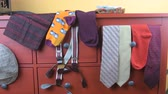 Mens garments. Clothing concept for men. Colorful socks, ties, braces, scarfs and checked flat cap on claret background. Classical concept of mens garments. Wintage typewriter and man clothing Vídeos