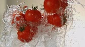 étvágygerjesztő : Flying tomatoes on a background of water. Very beautiful studio shot. Slow motion.