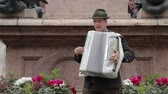 accordionist : An adult man plays an accordion in a national costume. Musical quartet playing. Musicians perform at the concert. The musician plays the accordion. Street musicians