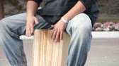 an : A street drummer musician plays a percussion instrument Cajon.