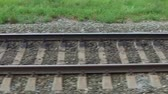 A view of the railroad tracks close-up of a passenger train window while moving from left to right.