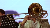caz : Close-up. A musician in a brass band plays solo on a trombone in white clothes.
