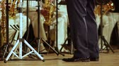 louisiana : The legs of a brass band in black trousers and patent shoes.