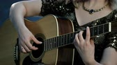 haarband : A girl with a necklace on her neck. The right hand touches the strings, the left hand holds the chords on the fingerboard. Smoke in the background. Day of music. Stockvideo