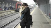 say goodbye : Young man kissing and saying and waving goodbye to his girlfriend in train station before leaving