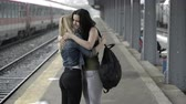 say goodbye : Sad young girls walking hand in hand in train station hugging  before separation Stock Footage