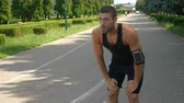 načasování : Handsome athletic man training on running track using wearable tracker gadget