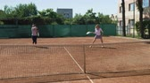 çiftler : Funny young women playing doubles at a tennis court Stok Video