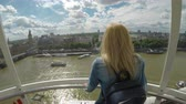 westminster : LONDON - JULY 2017: Young tourist woman in vacation admiring the Thames and cityscape from London Eye Millennium Wheel on vacation Stock Footage