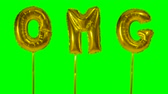 soletrar : Word OMG from helium golden balloon letters floating on green screen