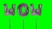 soletrar : Word wow from helium silver balloon letters floating on green screen