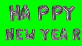 soletrar : Word Happy New Year greeting from helium silver balloon letters floating on green screen Stock Footage
